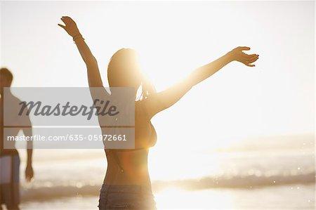 Woman in bikini cheering on beach