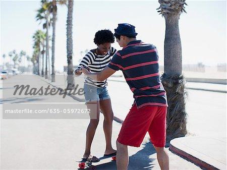 Man teaching girlfriend to skateboard