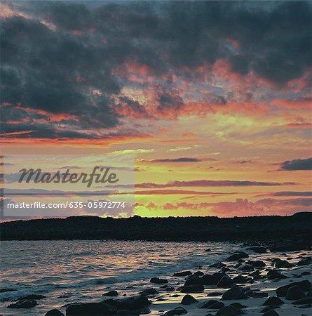 Sunset sky over rocky beach