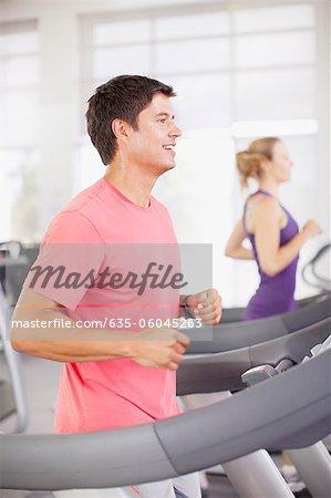 Smiling man running on treadmill in gymnasium