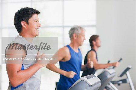 Men running on treadmills in gymnasium