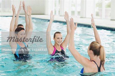 women taking water aerobics class in swimming pool stock photo