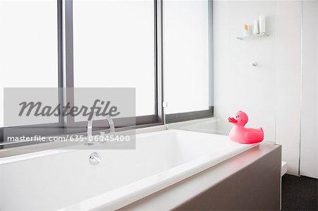 Pink rubber duck at edge of bathtub in modern bathroom