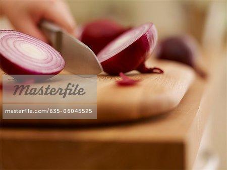 Knife chopping red onion on cutting board