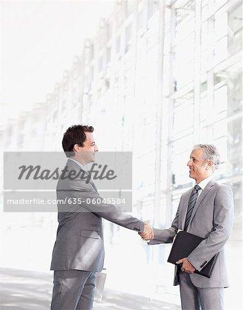 Smiling businessmen shaking hands in modern lobby