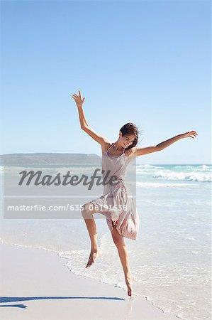 Carefree woman dancing on sunny beach