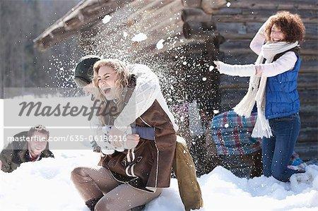Laughing friends enjoying snowball fight