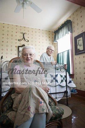 Portrait of feeble senior couple sitting in bedroom