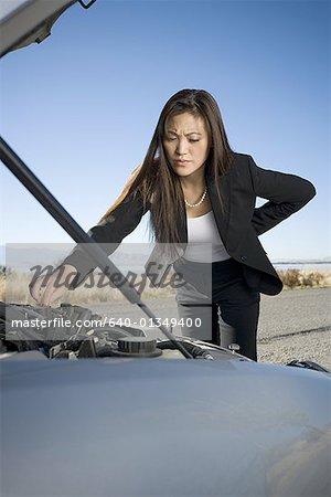 Woman repairing checking her car engine
