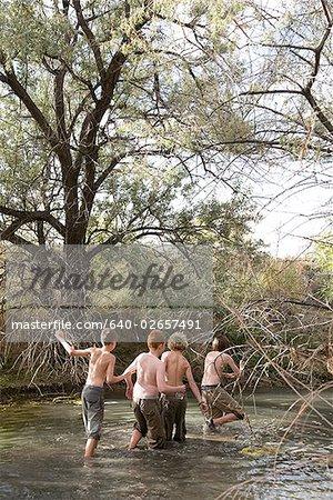 four boys crossing a river.