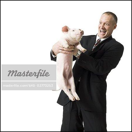 Businessman holding piglet