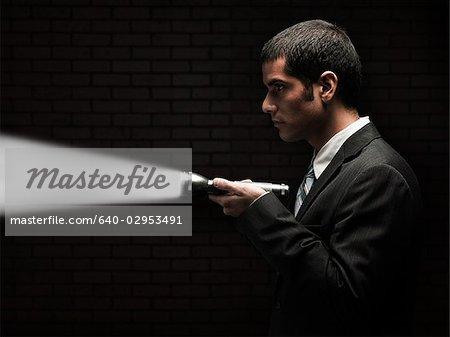 businessman holding a flashlight