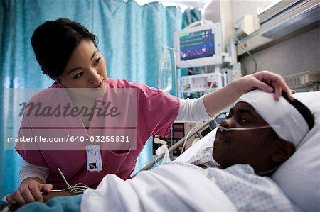 Nurse talking with boy in hospital bed