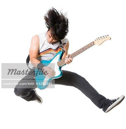 Young man jumping and playing guitar, studio shot