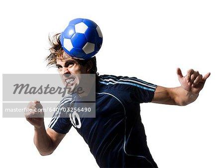Studio shot of man hitting soccer ball with head