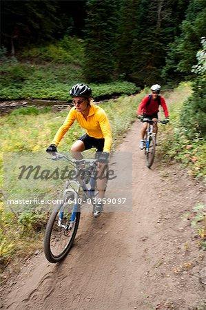 Man and woman biking on path outside