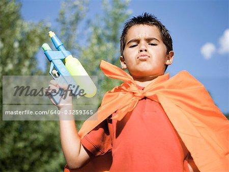 Boy in orange cape with water gun