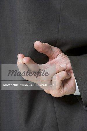 Fingers crossed behind businessman's back