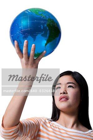 Teenage girl standing with a globe