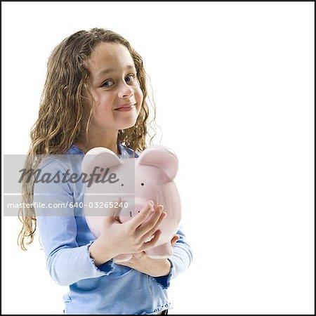 Young girl hugging piggy bank
