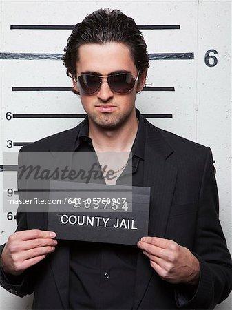 Studio mugshot of young man wearing sunglasses
