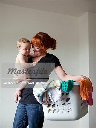 USA, Utah, Orem, Mother holding baby (6-11 months) and laundry basket