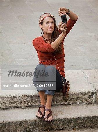 Italy, Venice, Woman using digital camera on steps