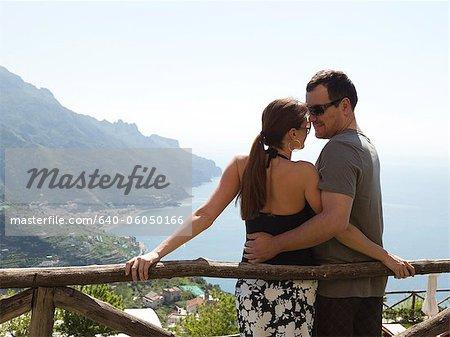 Italy, Amalfi Coast, Ravello, Mature couple standing together, coastline in background