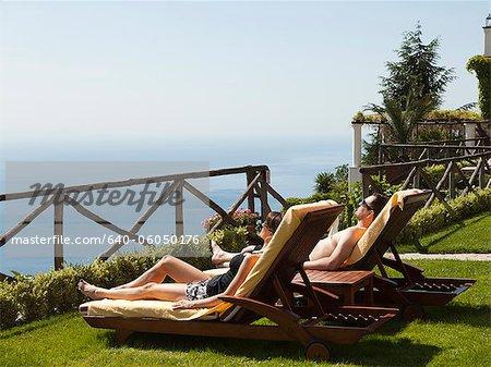 Italy, Amalfi Coast, Ravello, Mature couple lying on lounge chair
