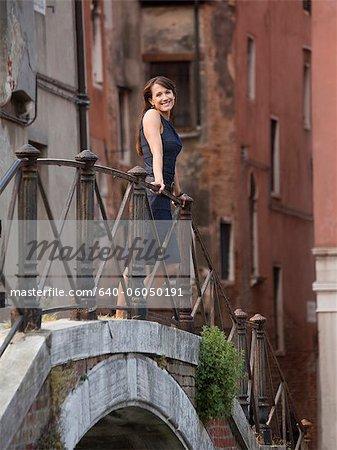 Italy, Venice, Portrait of smiling woman standing on footbridge