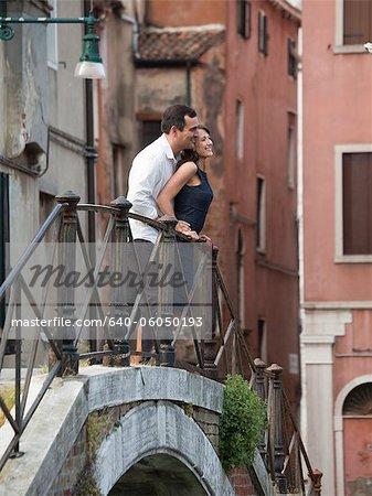 Italy, Venice, Romantic couple standing on footbridge