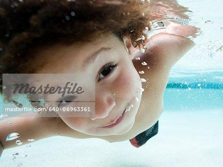 USA, Utah, Orem, Boy (4-5) swimming in swimming pool