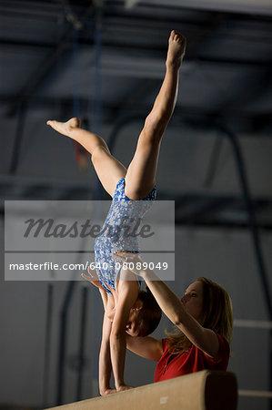 USA, Utah, Orem, coach assisting girl gymnast (10-11) on balance beam