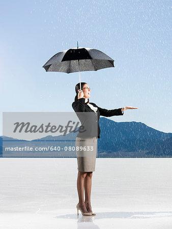 businessperson holding an umbrella in the desert