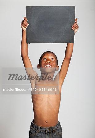 Studio portrait of boy (6-7) holding blank slate