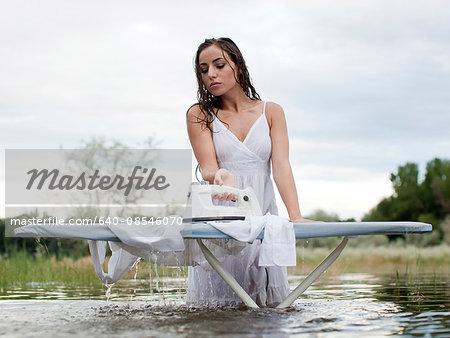 USA, Utah, Provo, woman wading in lake and ironing