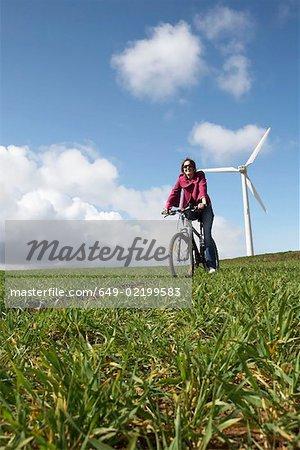 Woman riding a bike on a wind farm