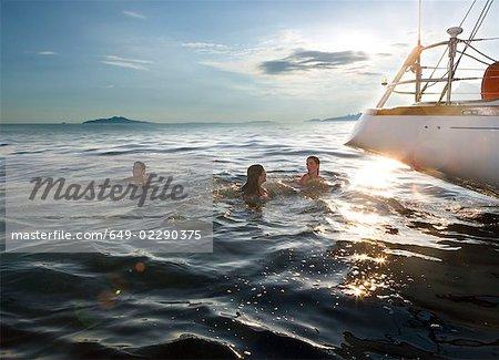 Three people swimming next to sailboat
