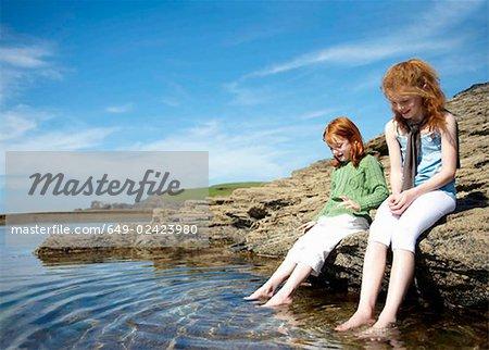 2 girls putting feet in rock pool
