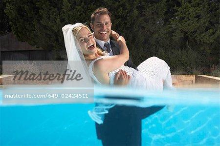 Groom carrying bride in pool