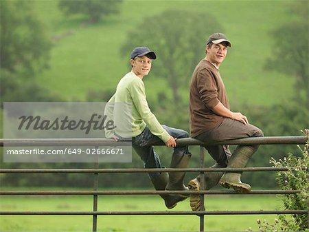 Farmer Talking To Son On Gate