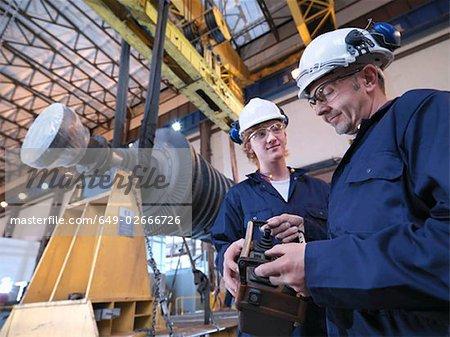 Engineers With Turbine And Crane
