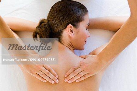 Hands massaging woman's shoulders
