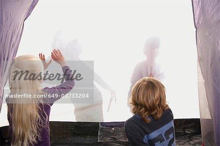 Children making shadows on tent