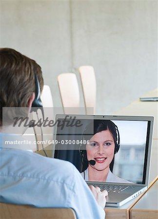 Businessman video calling colleague