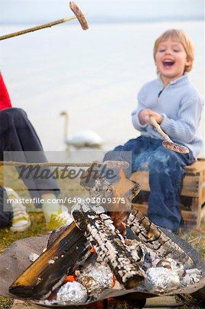 girl and boy roasting sausages on sticks