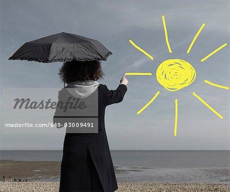 Woman painting sun onto grey sky