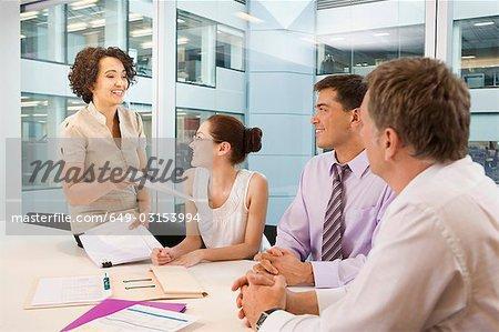 A senior female heads business meeting