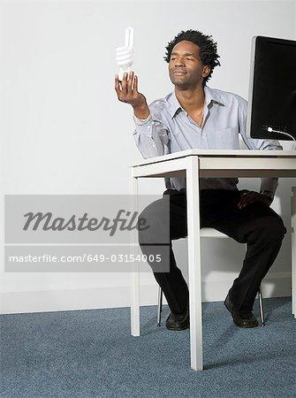 Business man holds up eco lightbulb