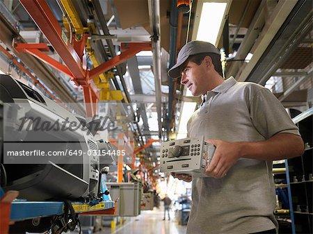 Worker Assembling Car In Plant